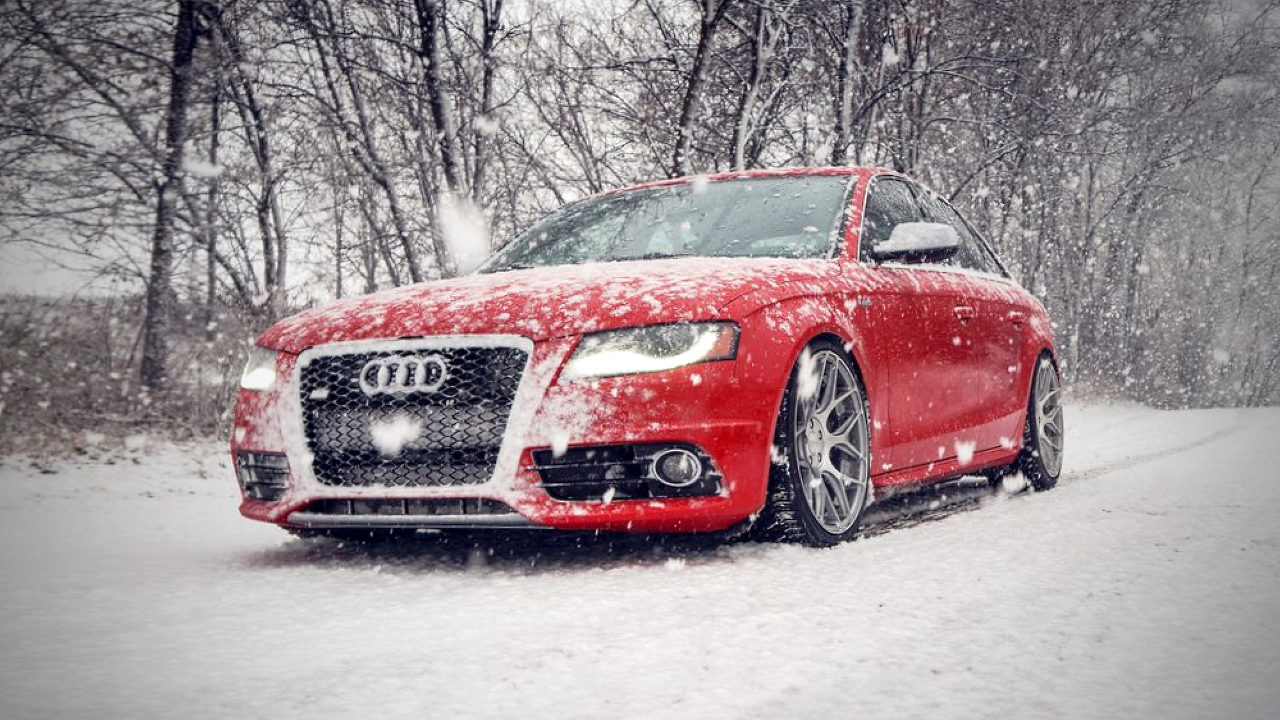 Автомобиль Audi едет по заснеженной дороге.