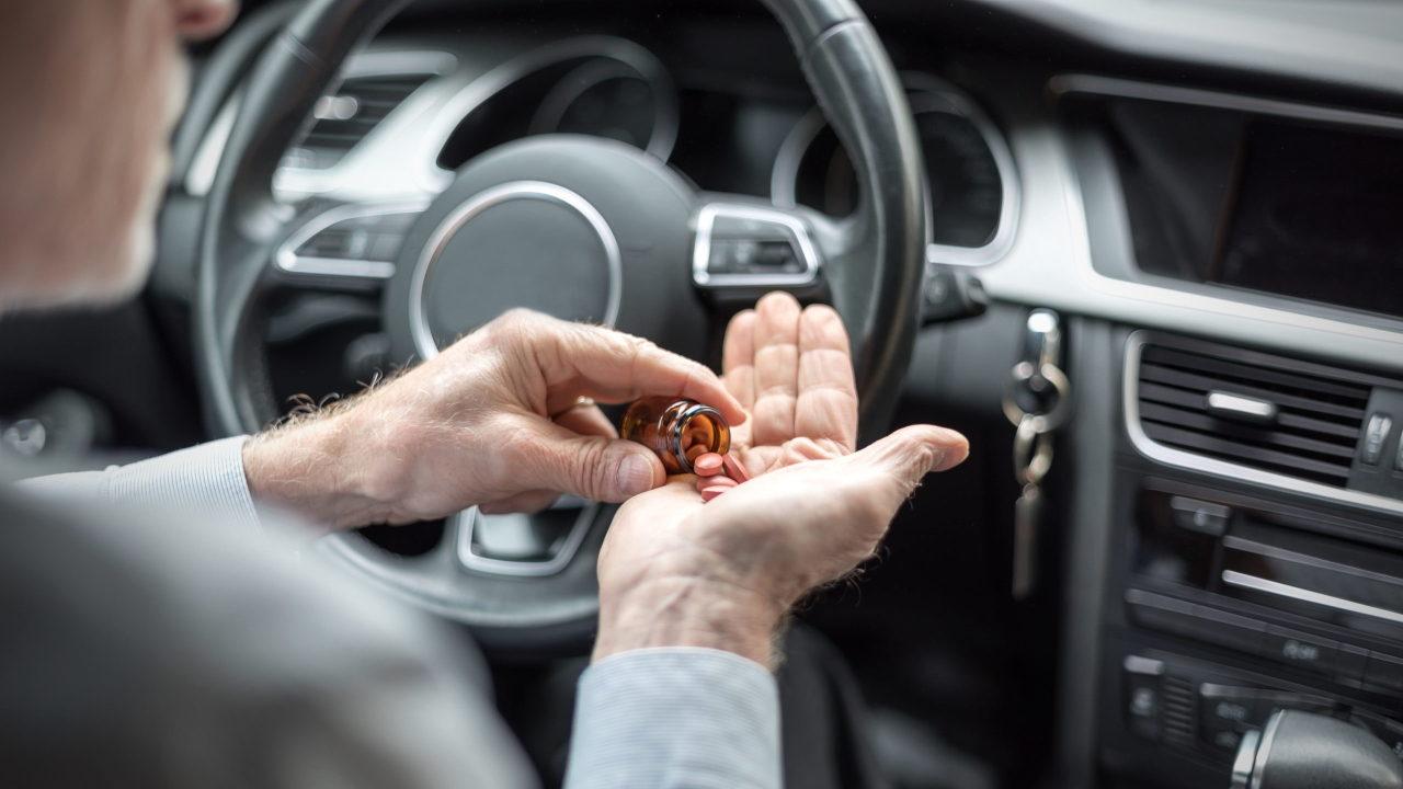 Водитель принимает лекарства за рулём автомобиля