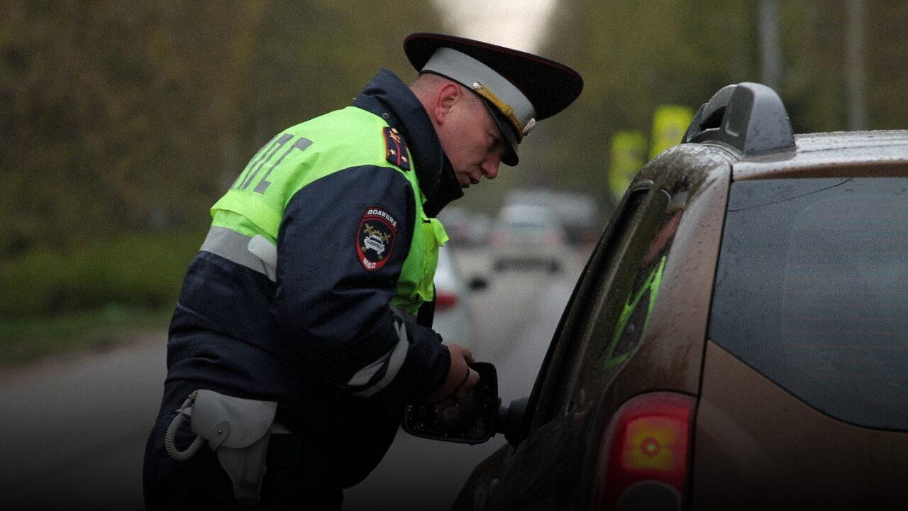Инспектор ДПС (ГИБДД) остановил автомобиль и проверяет документы